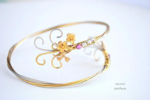 Gold coloured upper arm cuff with flower charm by IanirasArtifacts