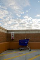 Shopping Cart on Roof with Sky by happeningstock