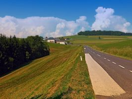 Country road and cloudy blue sky by patrickjobst