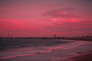 A crimson sunset over the beach by thead82